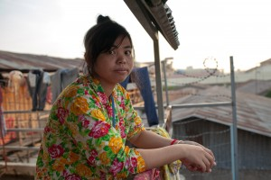 Win, a garment worker, outside her home in Phnom Penh.