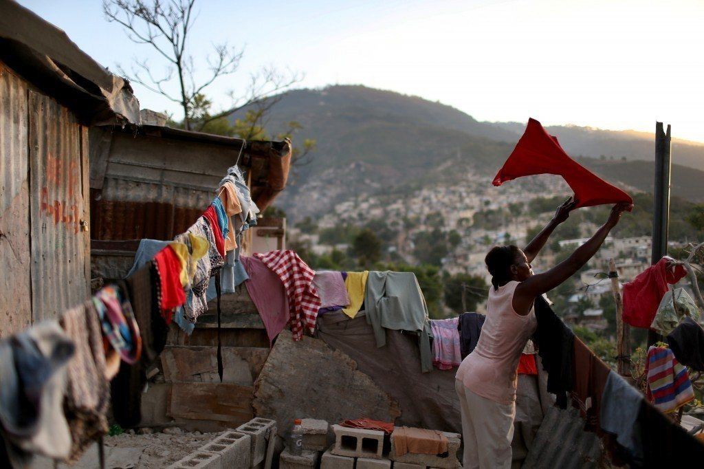 Woman hanging laundry in Haiti shantywon