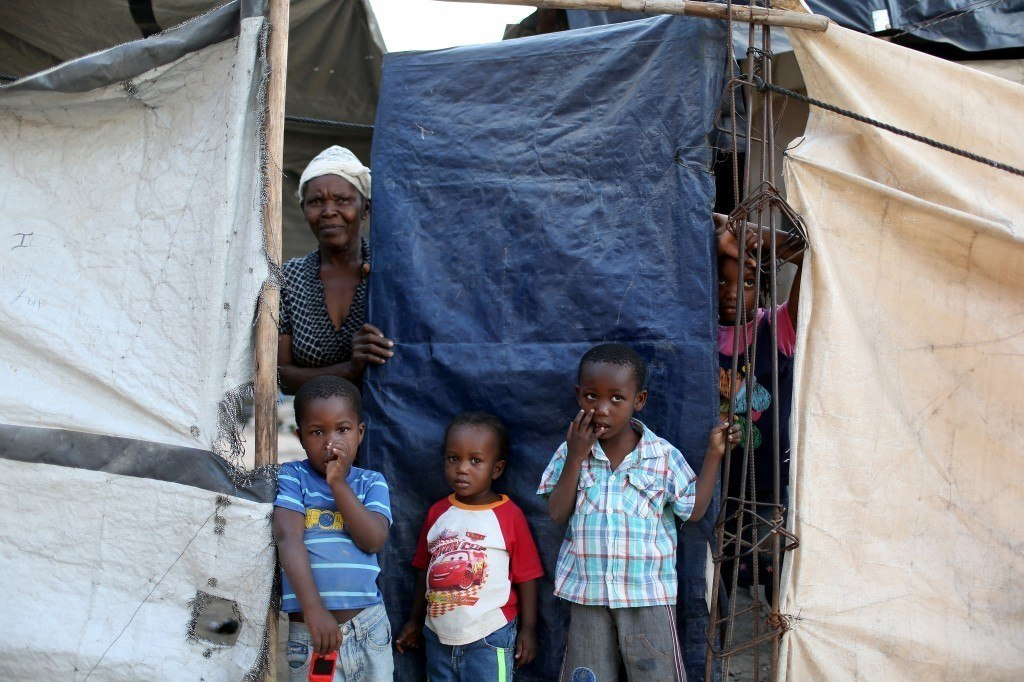 A family looks out from behind the tarp that serves as the front door to their home. Photo by Joe Raedle/Getty Images