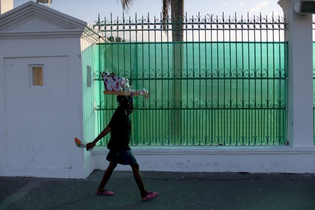 A woman walks past the fence that covers the view of what was the Presidential Palace before it was destroyed when magnitude 7.0 earthquake struck just before 5 p.m. on Jan. 12, 2010 in Port-au-Prince, Haiti. Photo by Joe Raedle/Getty Images
