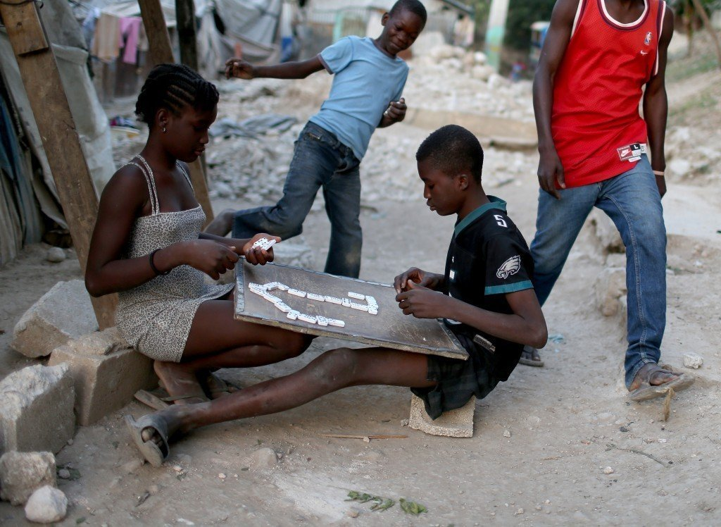 Children play a game of dominoes as they hang out together near their makeshift homes. Photo by Joe Raedle/Getty Images