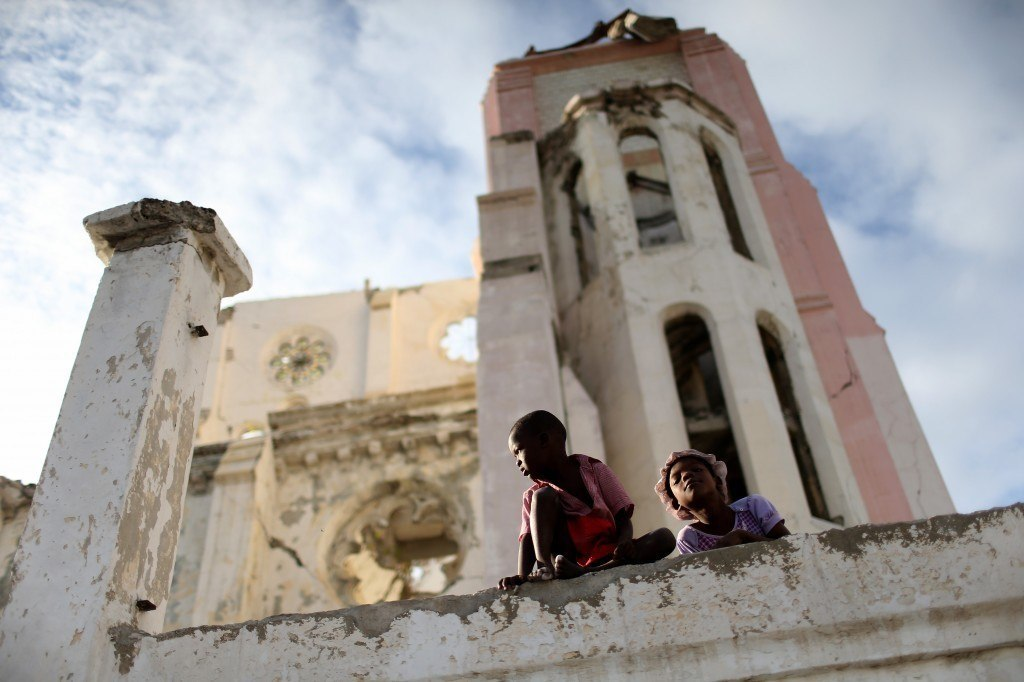 Children sit on the wall next to the National Cathedral that was destroyed five years ago by a magnitude 7.0 earthquake that struck Haiti in 2010. Five years later a church has been built next to the ruins and the city of Port-au-Prince struggles to recover even as the government is locked in a stalemate over parliamentary elections that have been delayed for several years. Photo by Joe Raedle/Getty Images