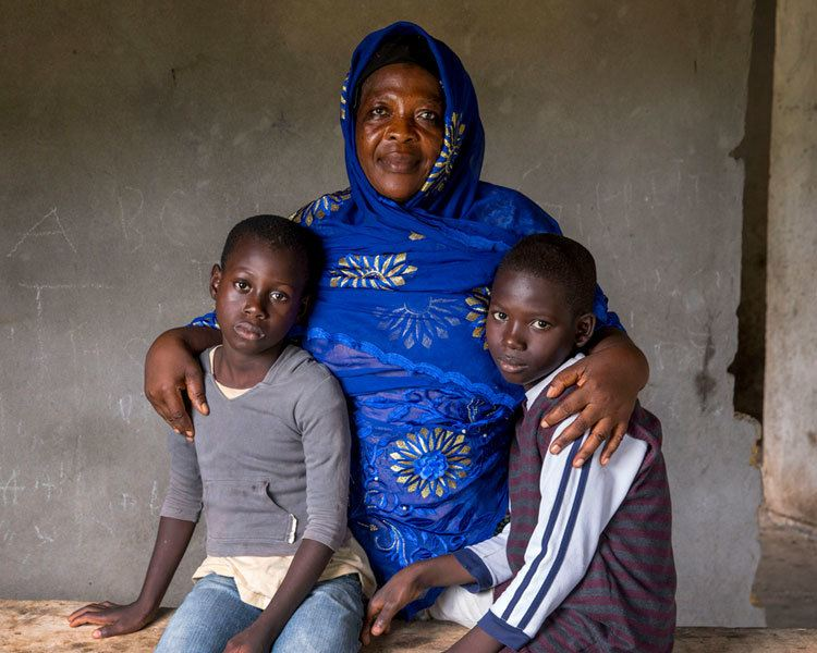 Vamuyan (left) and Kabune (right) lost both their parents to the Ebola virus in August 2014. Since then, their aunt Zainab Kaneh (center) has been caring for them at her home in Banjor, Liberia. (Photo by Jonathan Torgovnik)