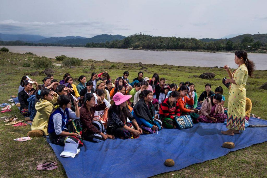 Women sit on a tarp near the river and participate in a community meeting with MRJ.