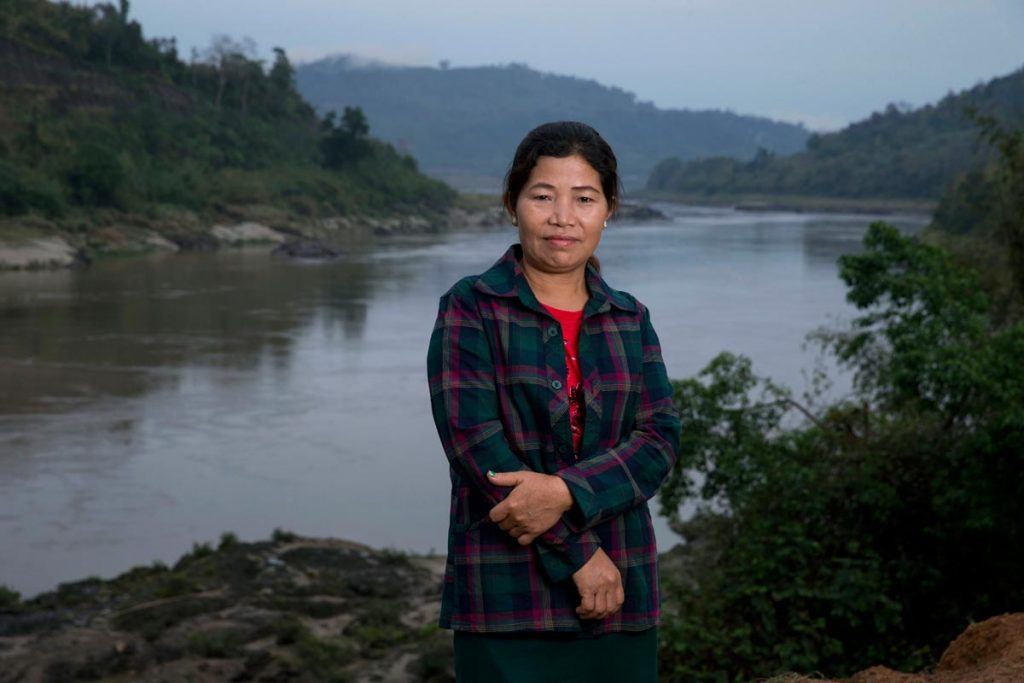 Ja Hkawn standing with her arms crossed on the bank of the Irawaddy River, near the proposed site of the Myitsone Dam