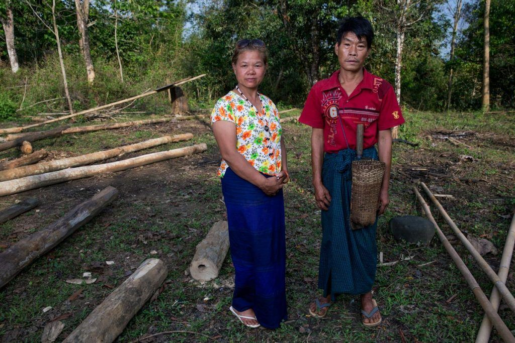 Lu Ra and her husband stand in a clearing at the site of their old home in their old village, where they are hoping to move back.