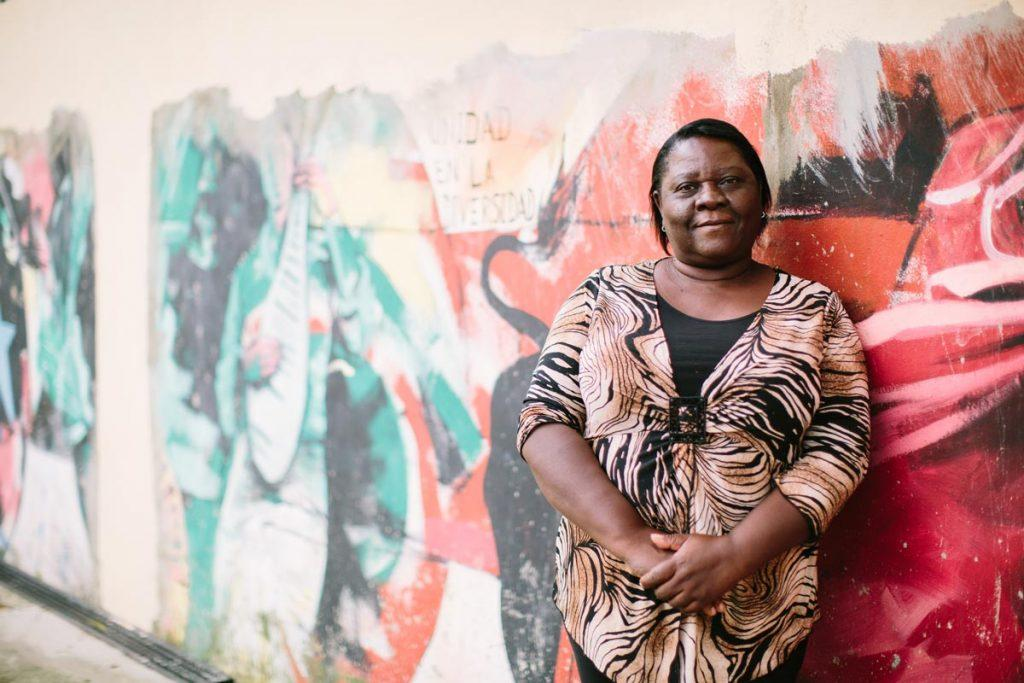 Germania Sevito, (standing in front of a colorful mural with her hands together, smiling softly) a Dominican of Haitian descent from Yacó Batey west of Santo Domingo, fought for access to her birth certificate for seven years. AJWS grantee Reconoci.do has helped her rise above the persecution she has faced because of her Haitian heritage. Photograph by Christine Han