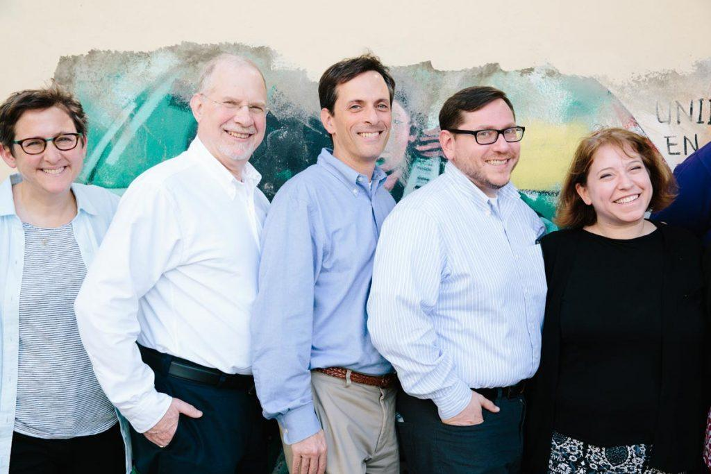 Rabbi Bruce Elder (center, wearing a blue shirt and smiling) standing in front of a colorful mural with colleagues Rabbis Sharon Kleinbaum (wearing glasses and a striped shirt), Sam Gordon (wearing a white shrit and glasses), Daniel Stein (in a light blue shirt and glasses) and Lauren Herrmann (wearing a black shirt) outside the offices of Reconoci.do, where the fellows learned about the Dominican citizenship crisis from people who have been affected by it.