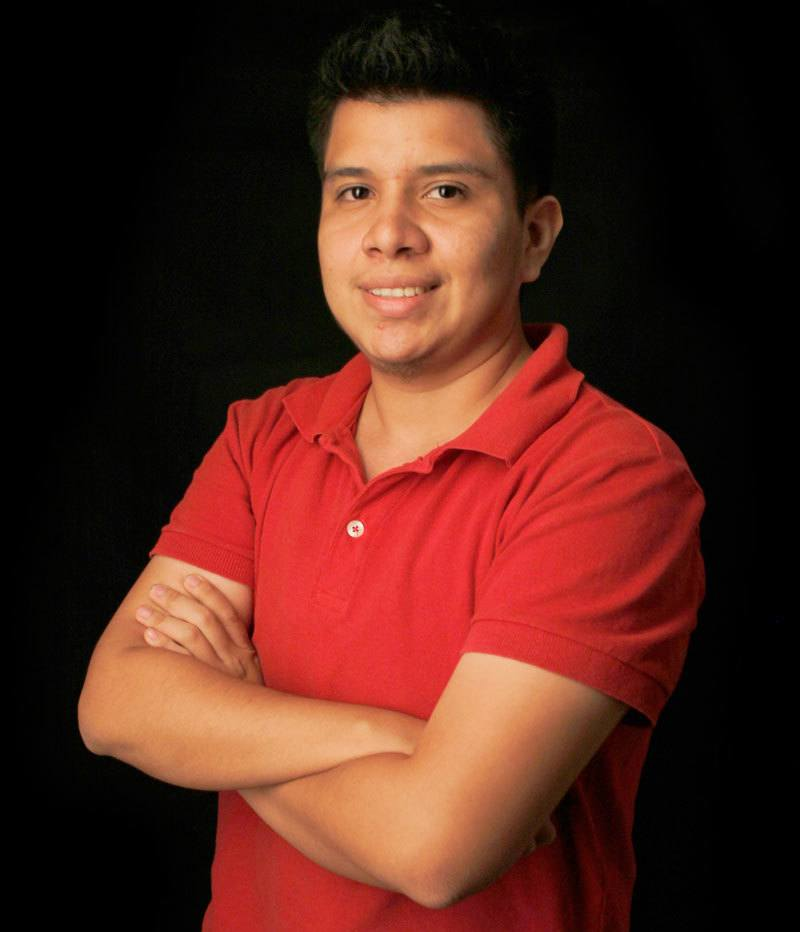 Sebastián Flores Cerritos, wearing a red polo shirt, crossing his arms across his chest and smiling at the camera.