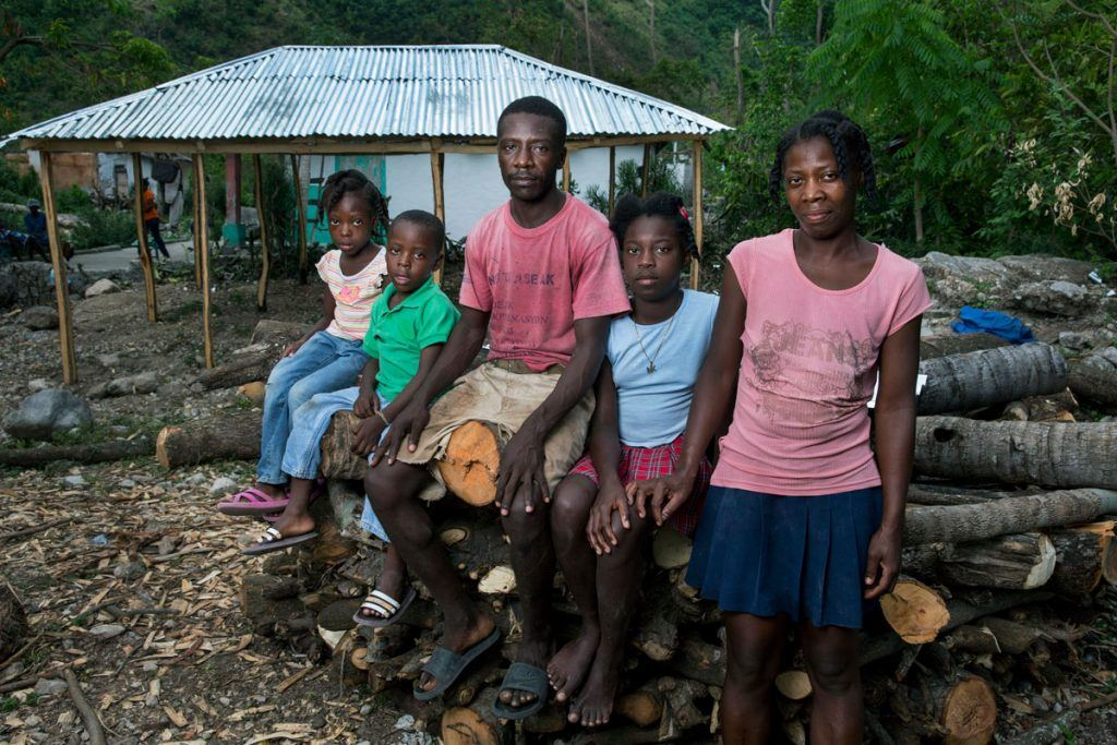 After Hurricane Matthew, AJWS grantee BDHH helped Nico and Perlage and their three children rebuild their home in the remote community Gwo Woch, on Haiti's southern peninsula. Here, the family members look at the camera with somber expressions while sitting on a pile of downed trees, near their new home with a tin roof. Photo by Jonathan Torgovnik