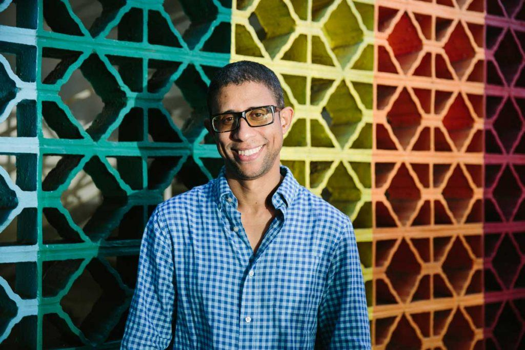 RevASA volunteer Deivis Ventura, wearing glasses and smiling in front of a colorful wall at the group's Santo Domingo office. Photograph by Christine Han