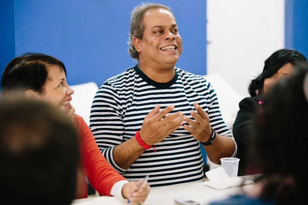 ASA director Leonardo Sanchez, smiling at the center of the photo and gesturing with his hands, tells AJWS Global Justice Fellows about the history of the Dominican LGBT rights movement. Photograph by Christine Han
