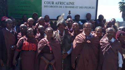 Members of the Ogiek, wearing dark red, standing outside the African Court following the landmark ruling. They are standing in front of a sign that indicates the name of the court. Photo by Gitahi Githuku