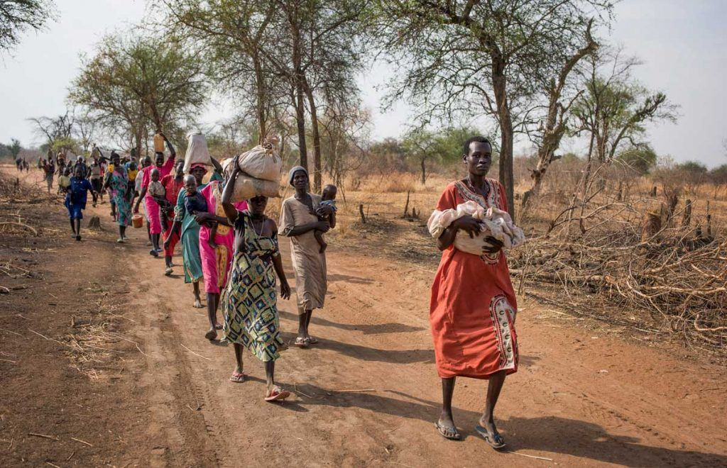 In this photo taken Wednesday, April 5, 2017, people walk for hours to reach a food distribution site in Malualkuel, in the Northern Bahr el Ghazal region of South Sudan. Two months after a famine was declared in two counties amid its civil war, hunger has become more widespread than expected, aid workers say, with the Northern Bahr el Ghazal region on the brink of starvation and 290,000 people at risk of dying without sustained food assistance. (AP Photo)