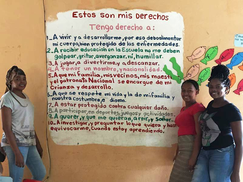 Teachers and volunteers stand by a sign that lists basic human rights for children. Because of poverty and discrimination, many children in Batey Palmerejo are living without all of these rights realized.